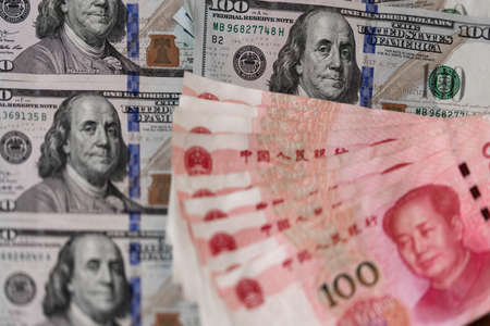 One hundred dollars and One hundred Chinese renminbi RMB bills. CNY background. Closeup of Benjamin Franklin and Mao Zedong . US dollars background. American currency.