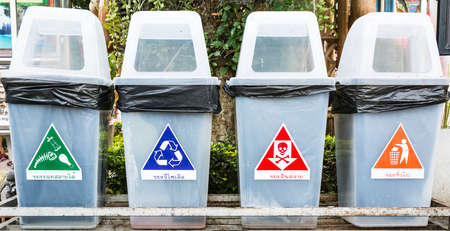 waste management: many color of waste icons with bins on stand near footpath concept waste management