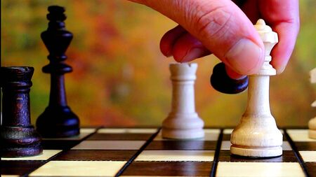 A hand is playing chess
