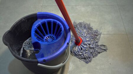 An used bucket of water with floorcloth on the ground