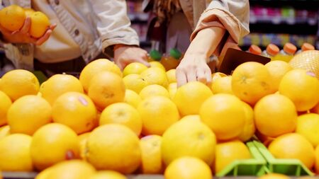 A man and a woman are buying oranges in a supermarket