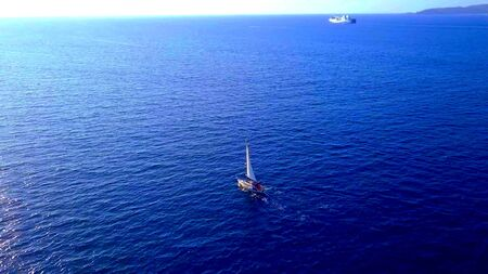 Aerian view of a sailboat on the ocean with the horizon