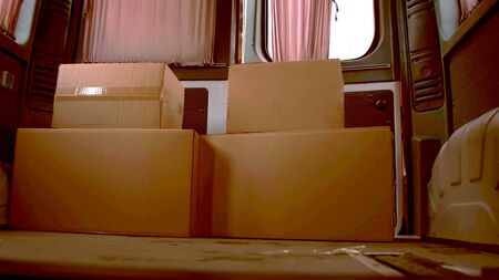 A photo of four carton boxes in the back of a van Reklamní fotografie