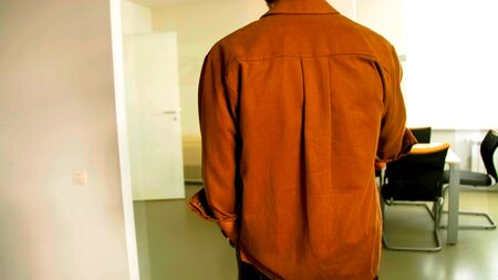 Photo of the back of a man who is coming in an office