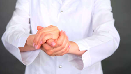 Photo of a woman in white coat who is rubbing her hands