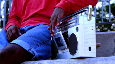 A photo of a black man who is using a vintage radio
