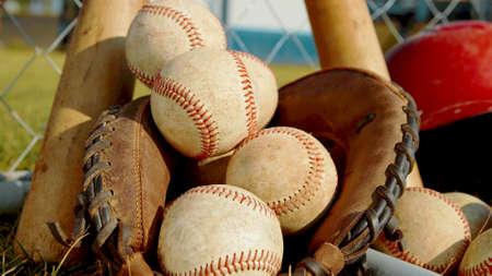 A close up on balls, a glove and bats of baseball