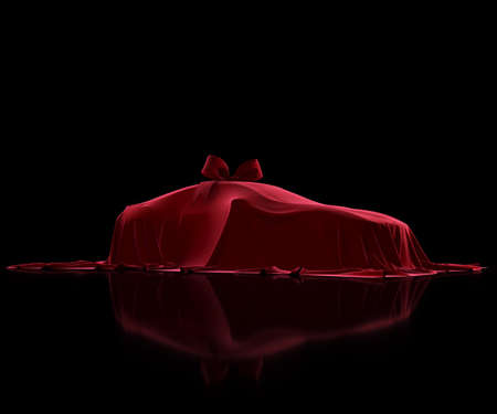Luxury car prize covered with premium fabric on a black background. Red velvet cloth. Surprise gift with a bow-knot Reklamní fotografie
