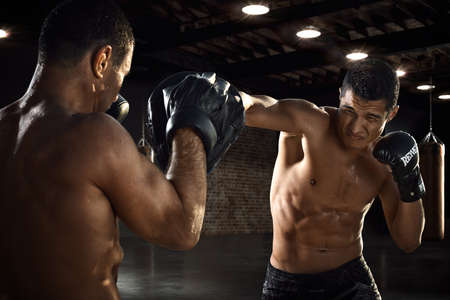 Fighter is training his boxing skills with a coach in a gym. Boxing, mma, wrestling, karate. Young, strong, muscular athlete