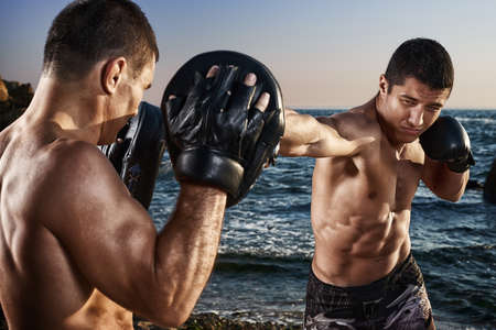 Fighter is training his boxing skills with a coach. Outdoor training on a beach. Boxing, mma, wrestling, karate. Young, strong, muscular athlete 免版税图像