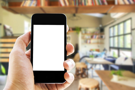phone business: hand holding phone with blurred library  background Stock Photo
