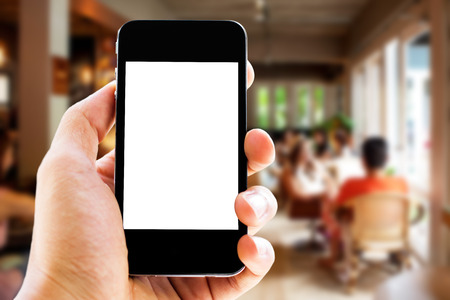 phone: hand holding phone with blurred cafe  background Stock Photo