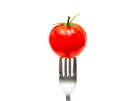 tomato and fork isolated on white background