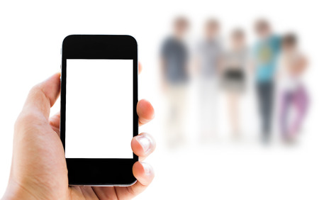 mobile telephones: hand holding phone on people background Stock Photo