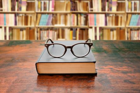 colegios: Libro con los vidrios en el escritorio frente a la biblioteca