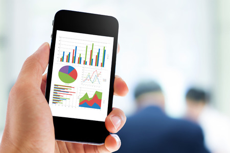 market analysis: hand holding mobile phone with analyzing graph