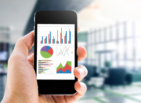 charts and graphs: hand holding mobile phone with analyzing graph