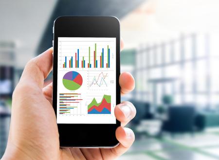 hand houden van mobiele telefoon met het analyseren van de grafiek