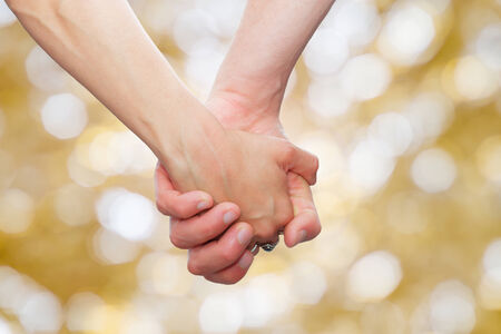 couple holding hands  on glittering background.background with bokeh defocused lights Archivio Fotografico