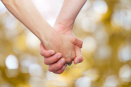 couple holding hands  on glittering background.background with bokeh defocused lights Stockfoto