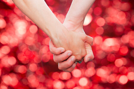 couple holding hands  on glittering background.background with bokeh defocused lights photo