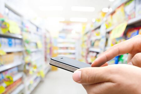 man on cell phone: Close up of hands man using his cell phone against super market background Stock Photo
