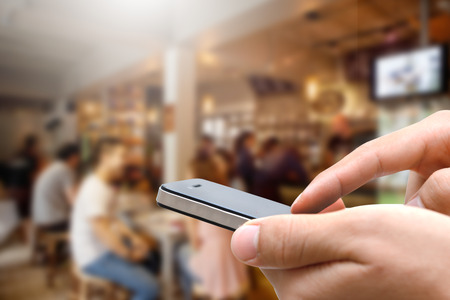 Close up of hands man using his cell phone against coffee cafe background Stock Photo