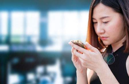 Candid image of young beautiful  asian woman use smart phone against business office background photo