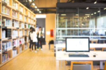 institution: Blurred background of modern library with people and bookshelves