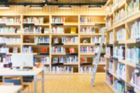 Blurred background of modern library with bookshelves