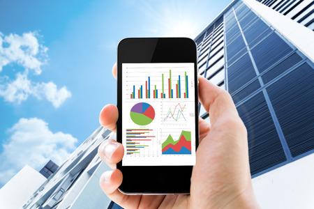 事務所ビルにおける太陽に対してグラフを分析すると携帯電話を持っている手