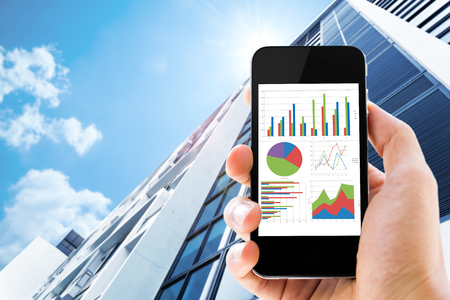 hand holding mobile phone with analyzing graph against office buildings with sun