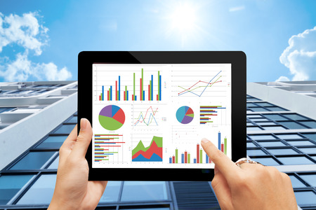 hand holding digital tablet  with analyzing graph against office buildings with sun Foto de archivo