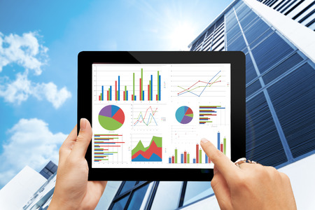 hand holding digital tablet  with analyzing graph against office buildings with sun Stock Photo
