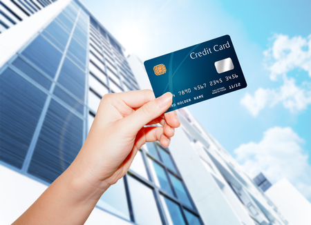 hand holding credit card against builind and sky