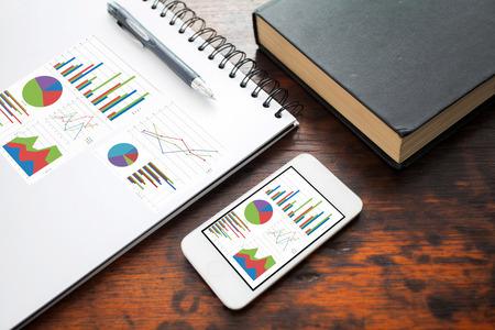 Analyse von Graphen auf Smartphone mit Notizbuch auf Bürotisch Standard-Bild - 39579475