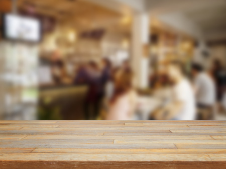 Empty wooden table and blurred people in cafe background, product display Foto de archivo