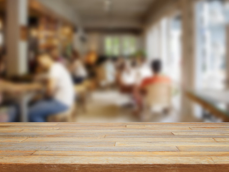 Empty wooden table and blurred people in cafe background product display