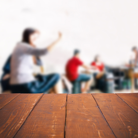 focus on background: Empty wooden table and blurred people in cafe background, product display Stock Photo
