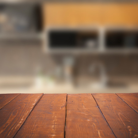 blurred background: Empty wooden table and blurred kitchen background, product display
