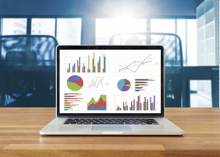 contabilidad: Computadora portátil en la mesa de madera que muestra los cuadros y gráficos contra el fondo de la oficina, Análisis de Negocios Contabilidad, Estadística Concept.