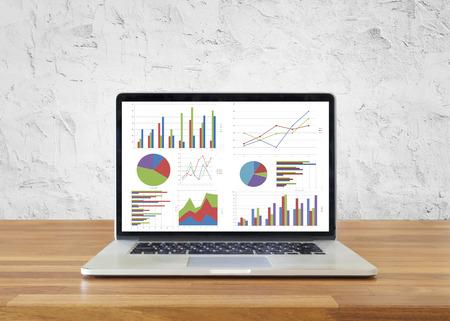 흰색 시멘트 벽, 분석 비즈니스 회계, 통계 개념과 차트 및 그래프를 보여주는 나무 테이블에 노트북입니다. 스톡 콘텐츠