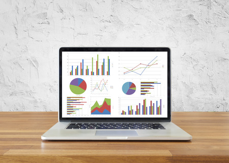 information symbol: Laptop on wooden table showing charts and graph with white cement wall ,Analysis Business Accounting, Statistics Concept. Stock Photo