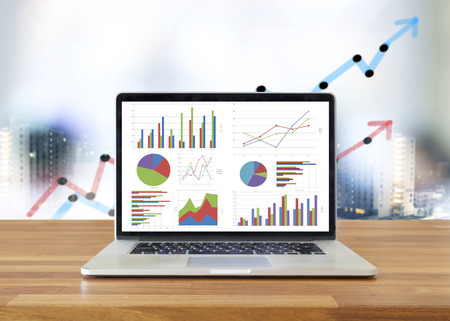 estadistica: Computadora portátil en la mesa de madera que muestran los cuadros y gráficos, análisis de negocio de Contabilidad, Estadística Concept.