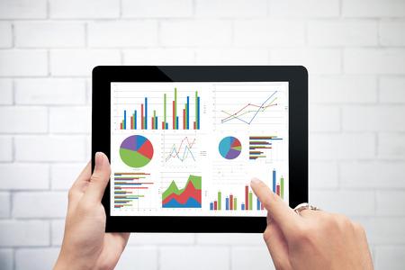 흰 벽 배경에 그래프를 분석하는 디지털 태블릿을 잡고 손을 닫습니다
