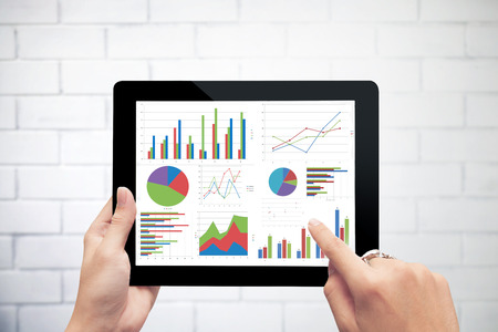 Close up hand holding digital tablet with analyzing graph against white wall background