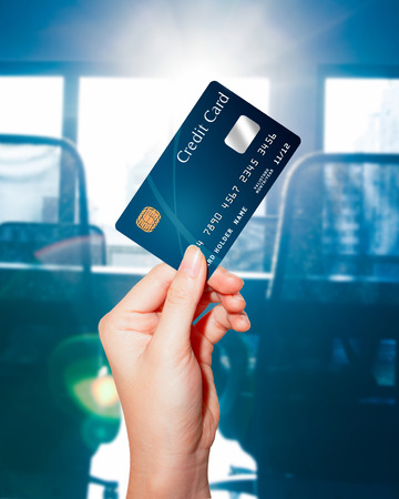 bank interior: female  hand holding credit card against business office background