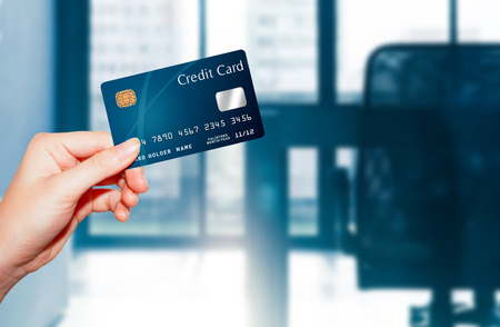 female  hand holding credit card against business office background