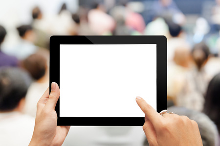 comercial: Close-up hand using digital tablet with blank screen against blurred people in business meeting