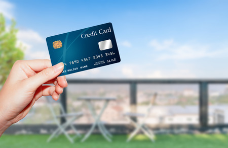 female  hand holding credit card against terrace view and bluesky Foto de archivo